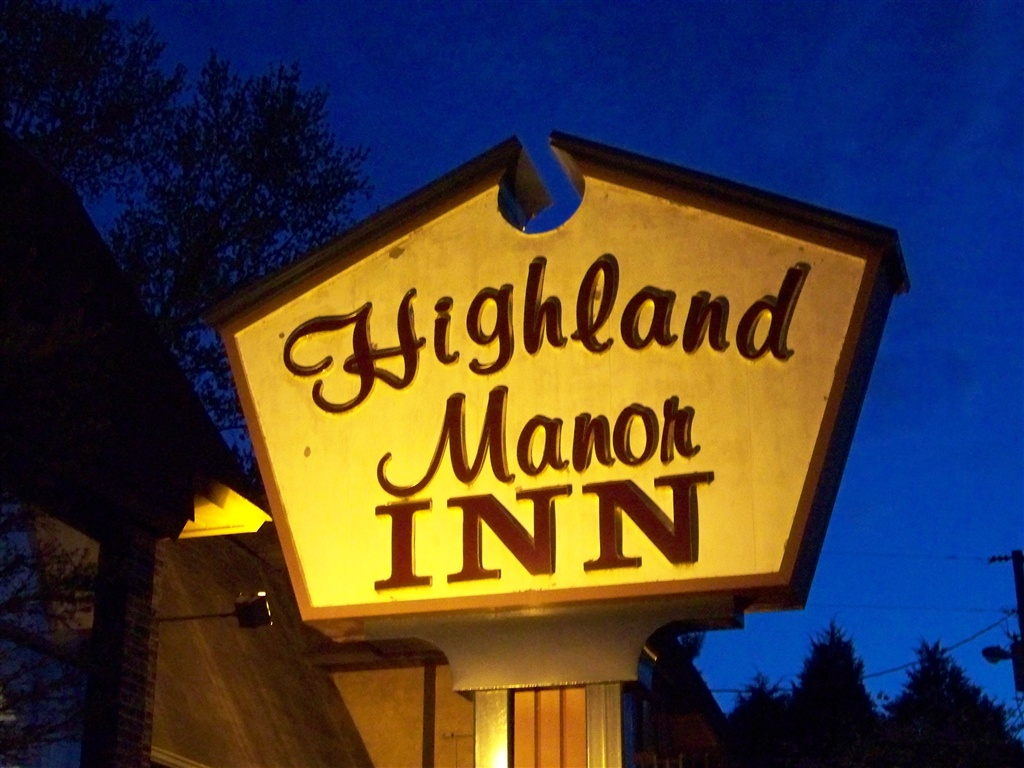 The Highland Manor Inn sign at night.