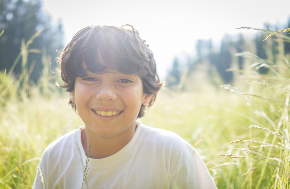 smiling young boy sitting in meadow in Townsend Tn