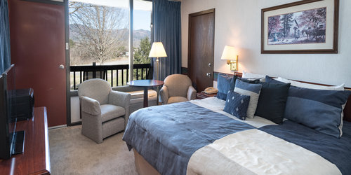 king bed with chairs and table by window with smoky mountain views jacuzzi and fireplace